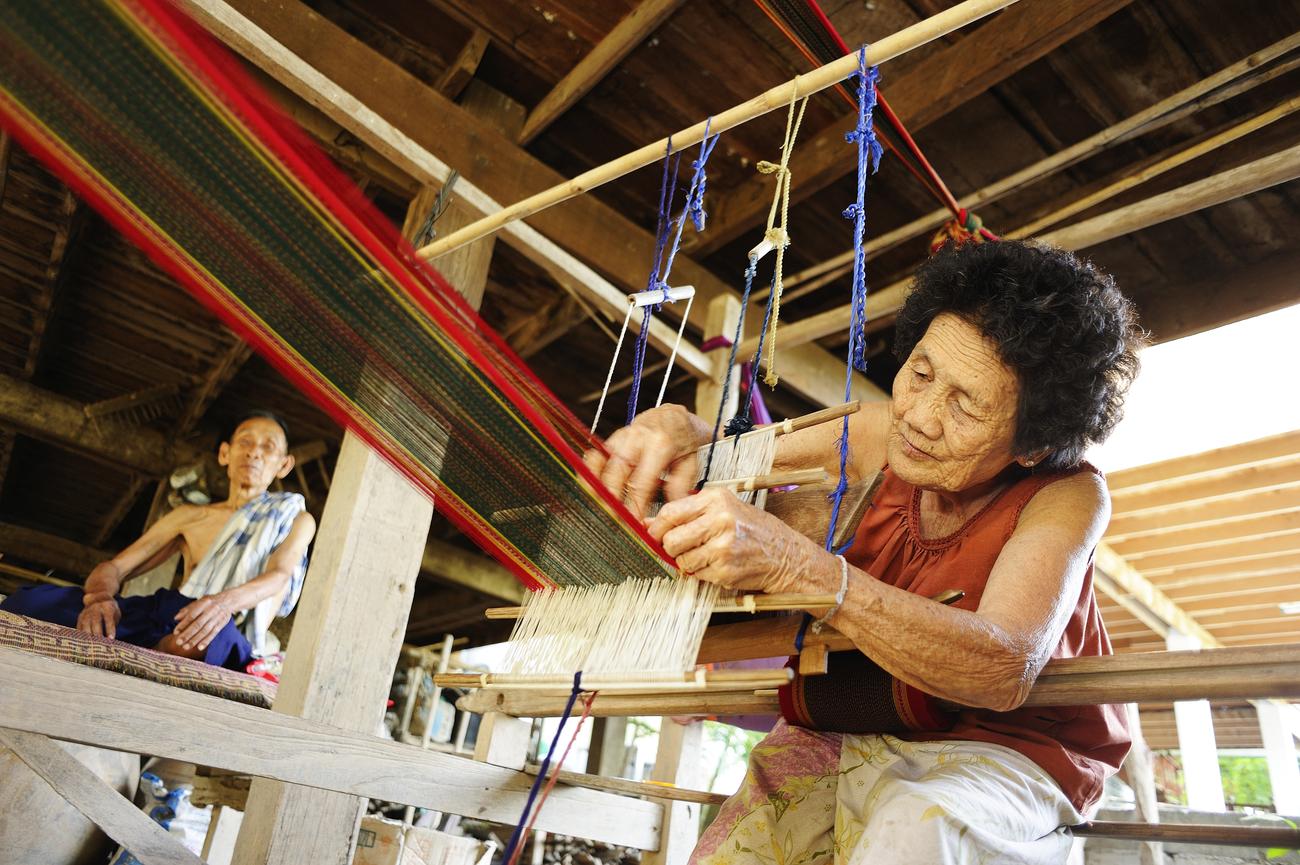 Thai textiles: Tai Phuan woman meticulously patterning Pha Sinh Teen Chok in Sukhothai